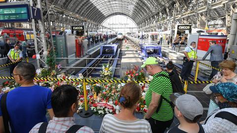 Passanten stehen am Gleis 7 des Hauptbahnhofs vor einem Meer aus Blumen, Kuscheltieren und Beileidsbekundungen.