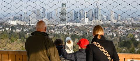 Eine Familie auf dem neugebauten Goetheturm genießt die Aussicht auf die Frankfurter Skyline