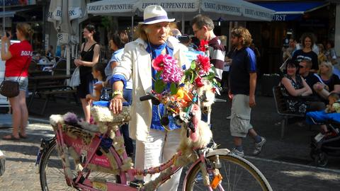Emmanuel de Greco in Anzug und mit buntem Fahrrad auf der Frankfurter Freßgass.