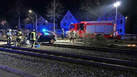 Auto nach Unfall auf Schienen, Feuerwehrleute