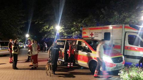 Helfer und Polizisten stehen neben einem Krankenwagen und einem Notarztwagen.
