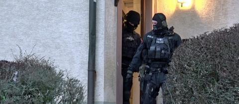 Polizisten kommen aus einer durchsuchten Wohnung im Rhein-Main-Gebiet.