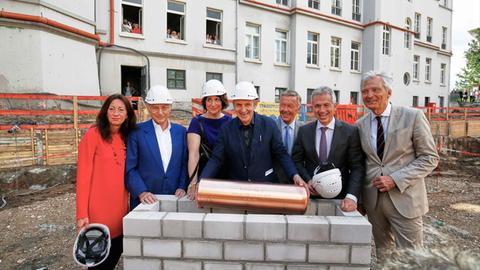 Grundsteinlegung mit OB Feldmann (2.v.r.): Eine Kartusche wird im Fundament des Museumsanbaus versenkt.