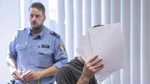 Der Angeklagte Ali B. versteckt sich hinter Akten