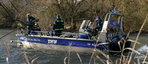 Einsatzkräfte des THW suchen von einem Boot die Fulda ab (Archivbild).