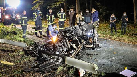 Einsatzkräfte der Feuerwehr stehen auf einem Waldweg im Halbkreis um ein ausgebranntes Wrack eines kleinen Hubschraubers.