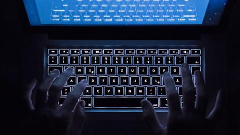 Hände tippen im Dunkeln auf einer Computertastatur