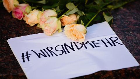 """Am Marktplatz von Hanau liegen Blumen und ein Zettel mit dem Schriftzug """"#WIRSINDMEHR"""""""