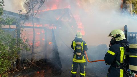 Zwei Feuerwehrleute löschen die brennende Gärtnerei.