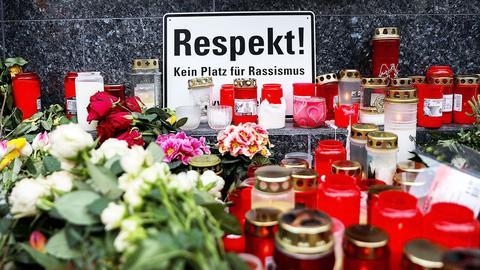 """Foto eines Gedenkortes in Hanau mit vielen Kerzen, Blumen und einem Schild: """"Respekt! Kein Platz für Rassismus"""""""