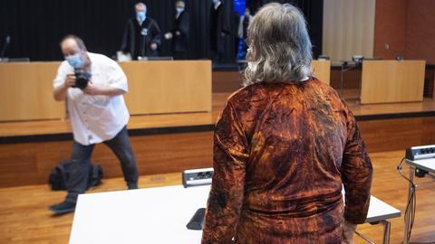 Frau von hinten zu sehen im Gerichtssaal, wird gerade fotografiert.