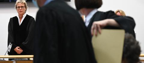 Susanne Wetzel (l), Vorsitzende Richterin am Landgericht Hanau, eröffnet den Prozess gegen eine 60-jährige Frau (r), die zusammen mit ihren Verteidigern auf der Anklagebank sitzt.