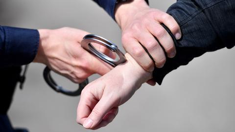 """Hände, die mit Handschellen andere Hände """"festnehmen""""."""