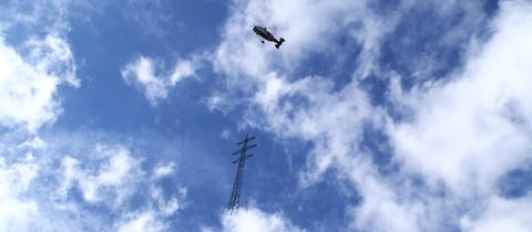 Ein Schwerlast-Helikopter transportiert einen Strommast im Odenwald ab