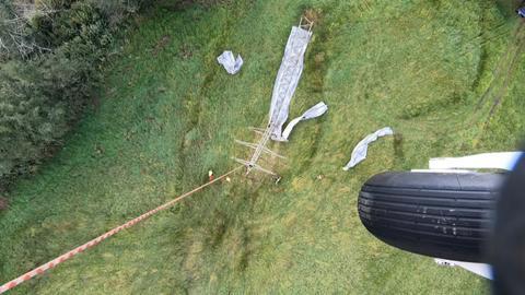 Blick aus dem Helikopter: Ein Strommast wird am Abschleppseil befestigt.