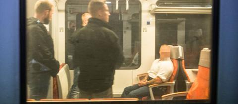 Der Angeklagte sitzt - bewacht von Sicherheitskräften - in einem Regionalzug am Herborner Bahnhof.