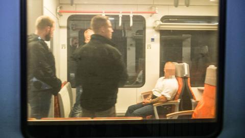 Der Angeklagte - bewacht von Sicherheitskräften - in einem Regionalzug am Herborner Bahnhof