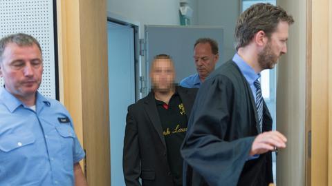 Der Angeklagte (M.) auf dem Weg zum Verhandlungssaal des Limburger Landgerichts
