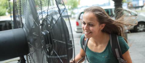 Eine Frau sucht Abkühlung vor einem Ventilator.