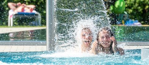 Jugendliche kühlen sich im Freibadbecken ab
