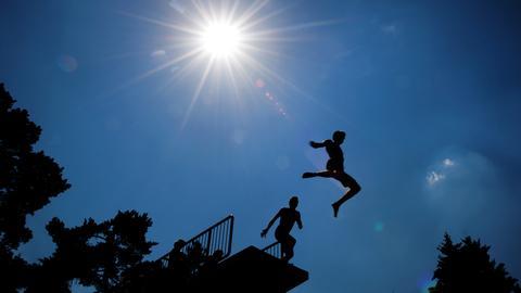 Zwei Kinder springen von einem Sprungturm im Schwimmbad