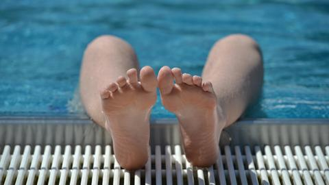 Ein Jugendlicher ist im Freibad Frankfurt-Eschersheim kurz abgetaucht, seine Füße liegen auf dem Beckenrand.