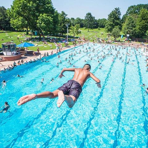Junger Mann springt vom Sprungturm im Schwimmbad ins Wasser