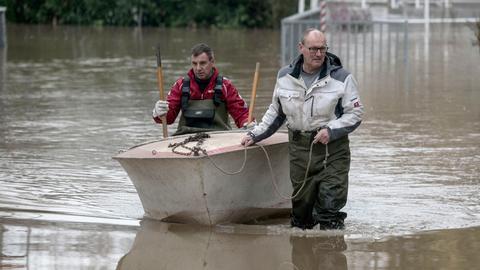 Mit einem Boot und Anglerhosen inspizieren zwei Männer den Stand des Hochwassers in Hattenheim.
