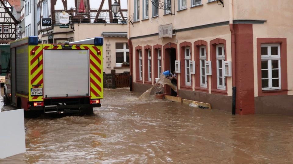 Die Feuerwehr fährt durch eine überschwemmte Straße in der Altstadt von Büdingen.