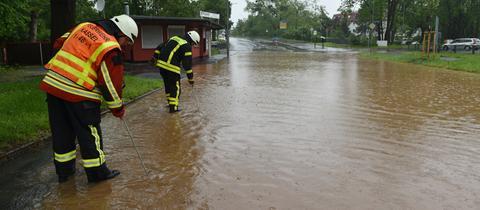 Feuerwehrleute in Kassel suchen mit Eisenstangen in einer überfluteten Straße nach dem Gullydeckel.