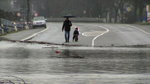 Straße überflutet, Mann und Kind auf Laufrad warten