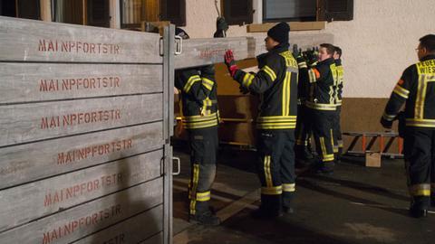 Feuerwehrleute bauen in Wiesbaden-Kostheim eine Hochwasserschutzwand auf.