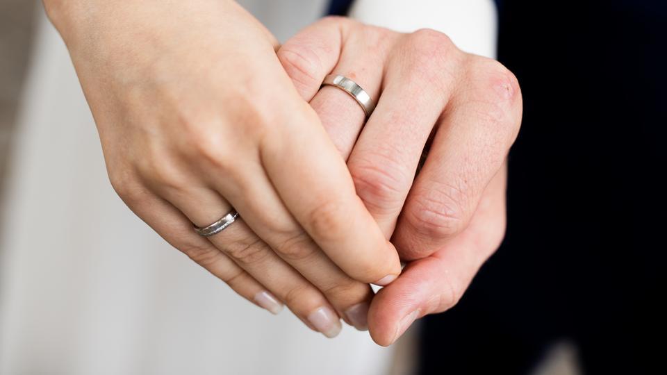 Die Hände von einem gerade vermählten Ehepaar, geschmückt mit Eheringen.