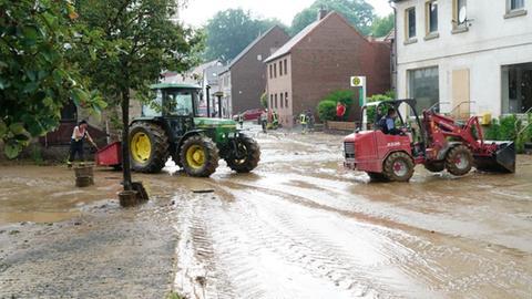 Aufräumarbeiten mit Traktoren auf Straße mit Schlamm