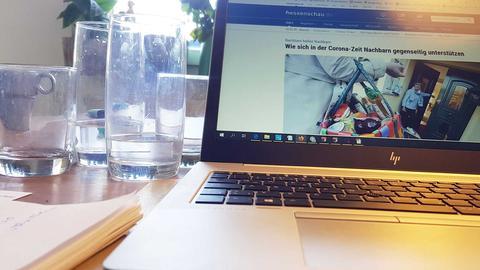 Vier benutzte Trinkgläser stehen neben einem Laptop auf einem Tisch.