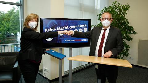"""Ministerin Kühne-Hörmann und hr-Intendant Krupp üben einen coronagemäßen Handschlag aus. Im Hintergrund ein Bildschirm mit einer Grafik mit der Aufschrift """"Keine Macht dem Hass"""" und vielen Logos."""