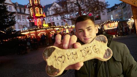 Weihnachtsmarkt-Verkäufer mit Keks-Knochen für Hunde