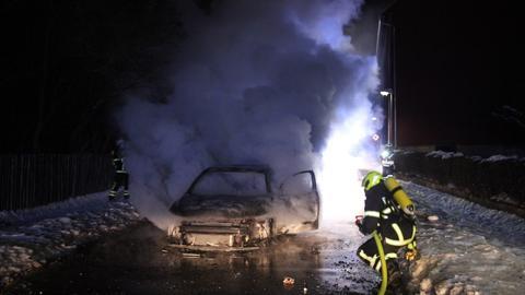 Die Feuerwehr löscht das brennende Hybrid-Auto.