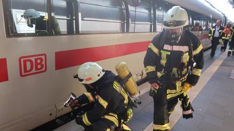 Feuerwehrleute mit Atemschutzmasken untersuchen den ICE.
