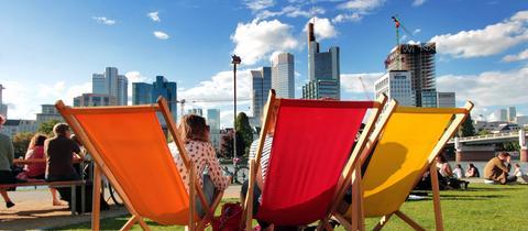 Frankfurter genießen den Sommer und die Sonne vor der Skyline