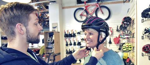 Ein Verkäufer hilft einer Kundin beim Anprobieren eines Fahrradhelms.