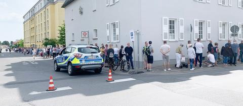 Sehr viele Menschen stehen entlang einer Straße und um eine Hausecke herum Schlange. Daneben ein Polizeiauto.