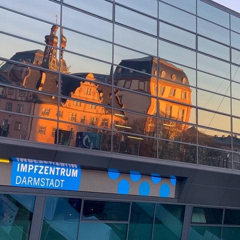 """Glasfassade eines Gebäudes, in dem sich städtische Gebäude in der Abendsonne spiegeln. Über der Eingangstür steht auf einem Schild """"Impfzentrum Darmstadt""""."""