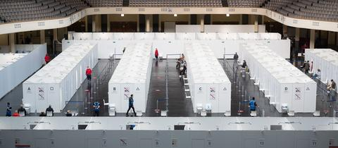Das temporäre Impfzentrum in der Frankfurter Festhalle von einem der Ränge fotografiert. In der Mitte sind weiße Kabinen aufgebaut.