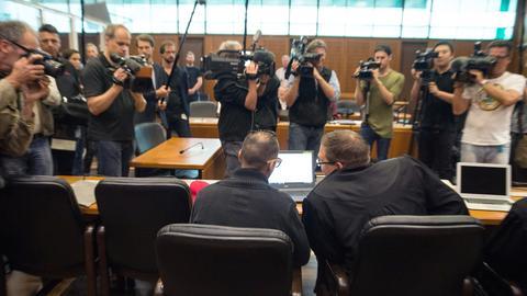 Der Angeklagte (l.) und sein Anwalt im Gerichtssaal - vor sich eine Gruppe von Kameraleuten.