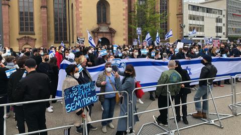 Hinter einer Absperrung stehen die Gegendemonstranten mit Israel-Flaggen.