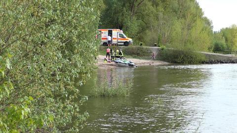 Jetski und Feuerwehrleute am Ufer eines Flusses.