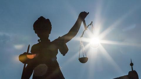Die Morgensonne scheint von hinten in Frankfurt auf dem Römerberg auf die Figur der Justitia auf dem Gerechtigkeitsbrunnen.