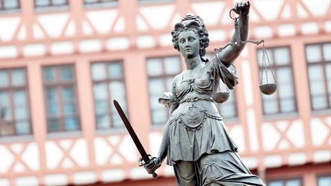 Statue der Justizia vor einer historischen Fachwerkhausfassade.