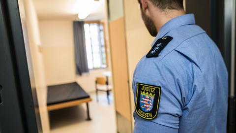 Ein Justizvollzugsbeamter steht in der JVA Frankfurt I vor einem Einzelhaftraum.
